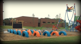 Tires and outdoor chalkboard installed on a playground at an Elementary School in Raleigh NC to help children continue developing gross motor skills while playing in a colorful environment.